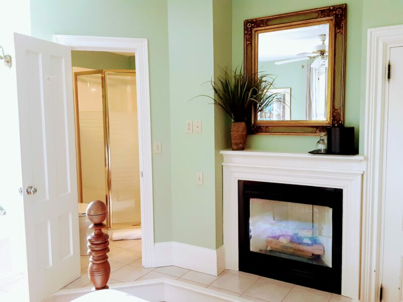 A lovely room with gas fireplace stove and a mirror over it