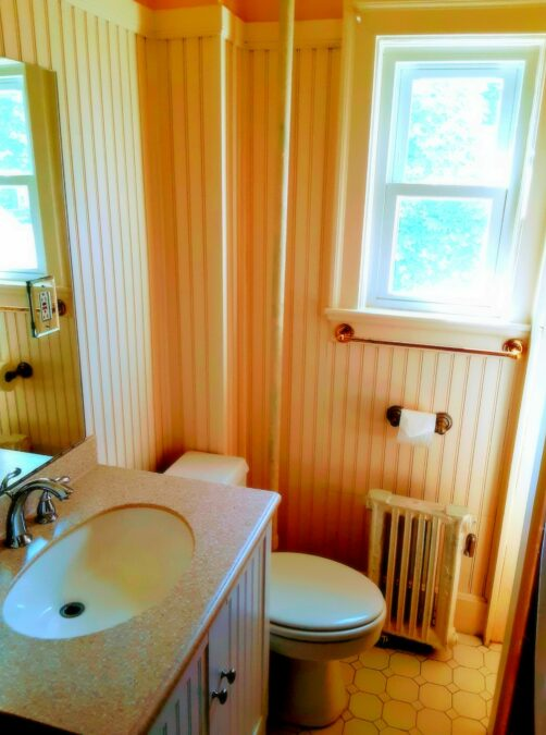 A bathroom is shown with granite sink