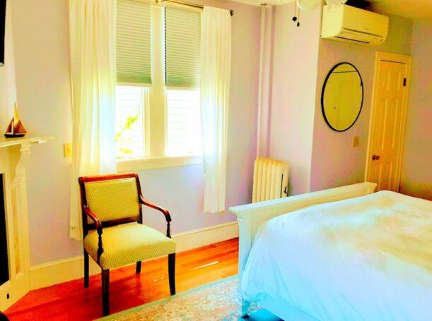 A queen bed faces 2 bright windows