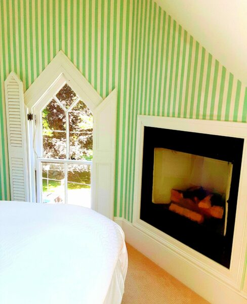 A gas fireplace faces a guest bed