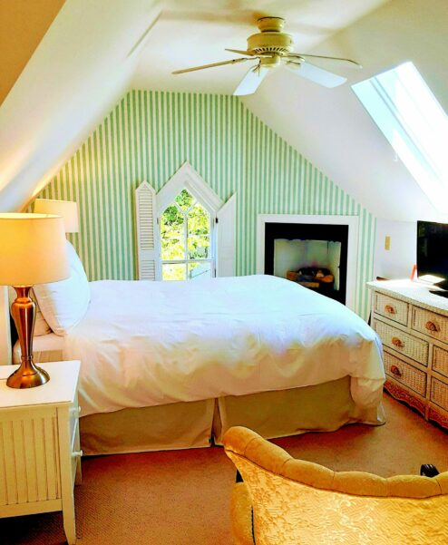 A room is shown with chirch window and green striped wall paper