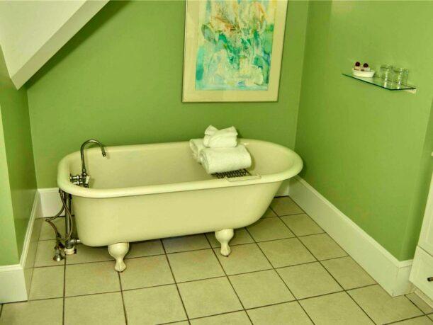 A clawfoot tub sits in a green bathroom