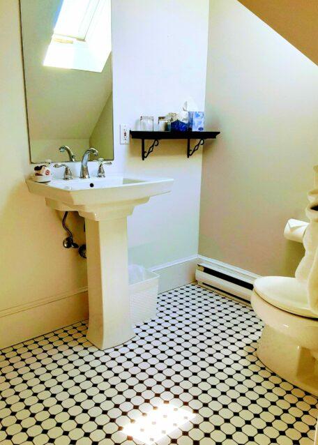 A tiled floor bathroom has a skylight