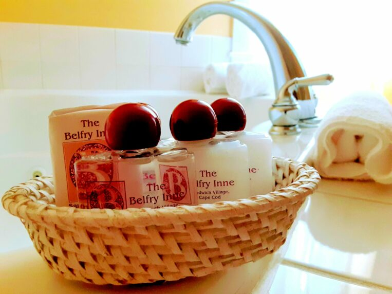 A basket of bath amenities sits on the edge of a tub