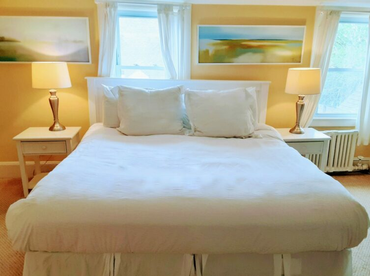 A queen bed is with 2 bedside tables with lamps and a painting