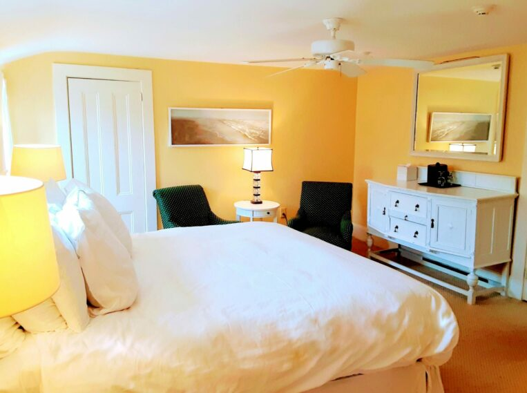 Photo of a guest room with yellow walls and a white bed