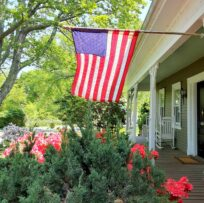 An American flag flies over an old front porch