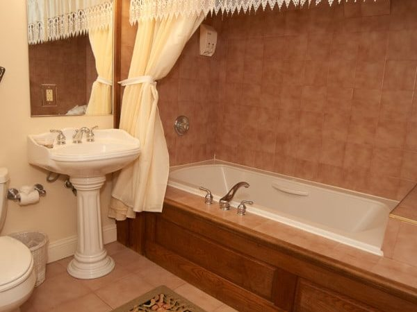 A lovely Jacuzzi tub is shown with brown tiles