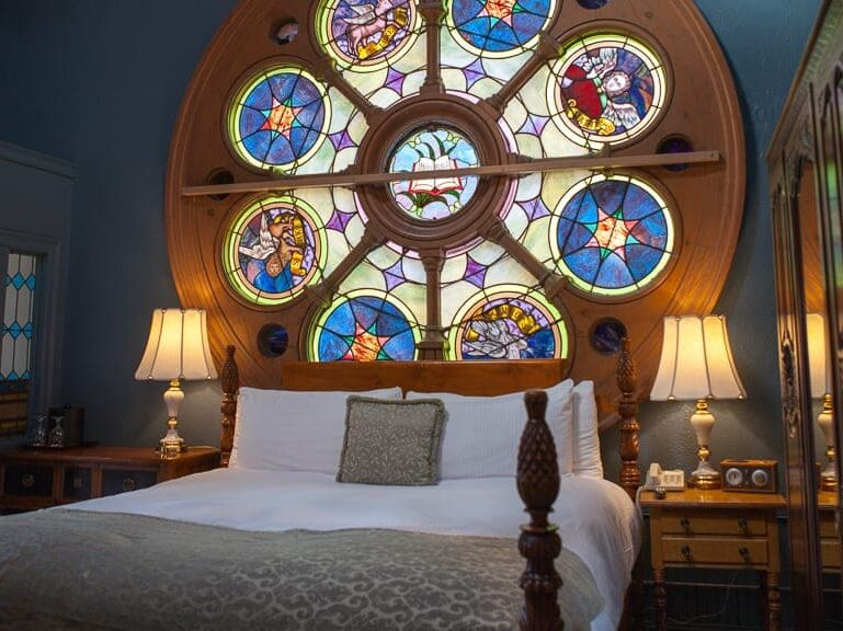 A bed woth a large stained glass behind it