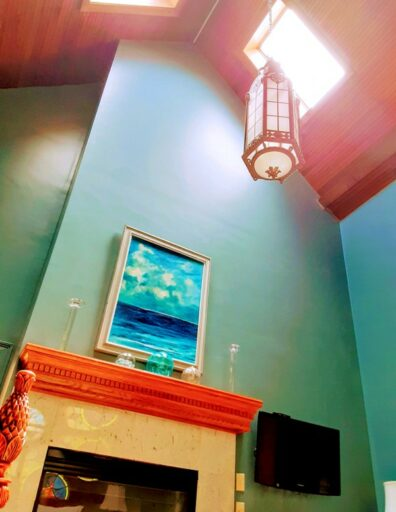 A church lantern hangs over a fireplace in a high ceiling room