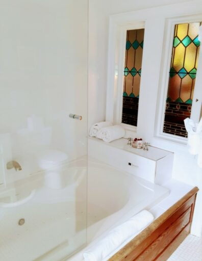 A jacuzzi is shown with stained glass at the foot of it