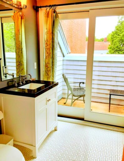 A bathroom is shown with a small balcony attached