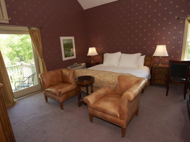 A king bed in a maroon room faces a deck