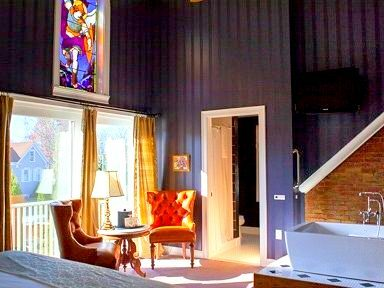 A blue colored guest room has a brightly colored stained glass mural