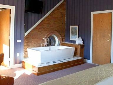 A large tub sits in the center of a guest room
