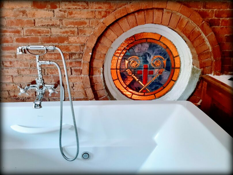 a clawfoot bathtub has stained glass behind it