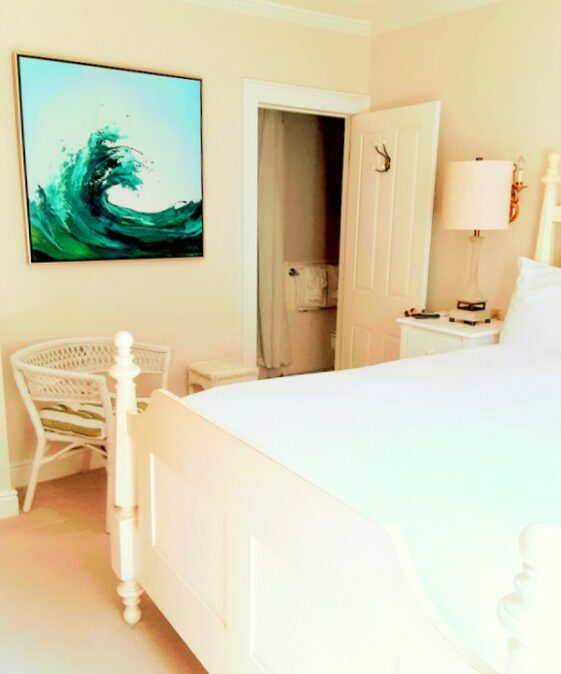 A queen bed is shown with giant wave painting and a bathroom