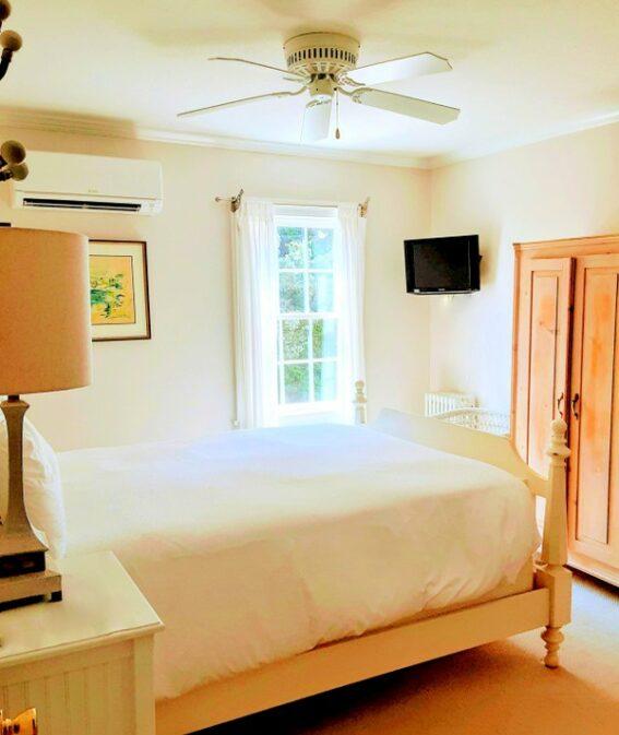 A queen bed faces a wooden dresser