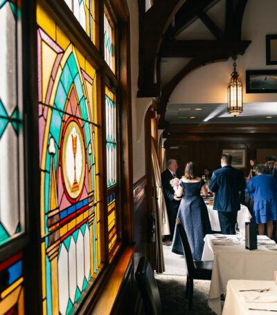 Folks gather near the Bistro stained glass window