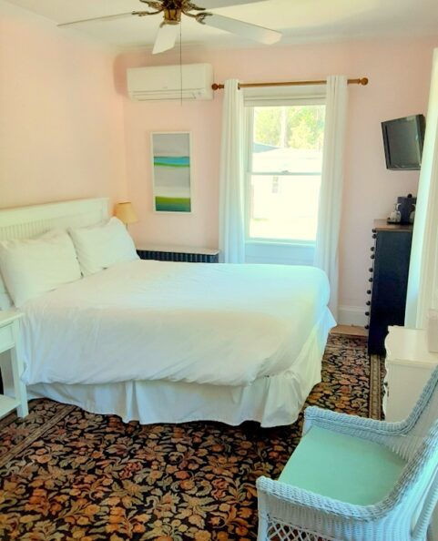 A chair and queen bed are in a pink bedroom