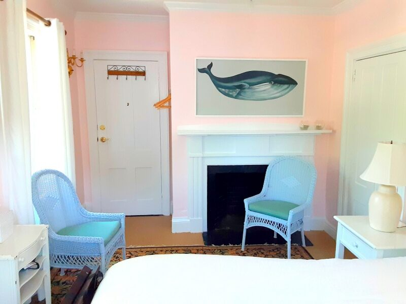 A pink guest room shows a fireplace with a whale painting over it