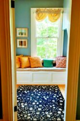 Brightly colored pillows adorn a white bench