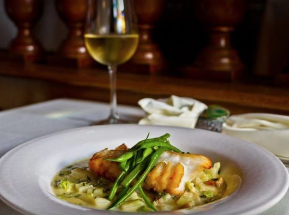 A filet of seared fish rests over a bed of risotto and is topped with green beans.