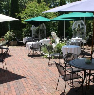 Outdoor tables and chairs are set at lunch