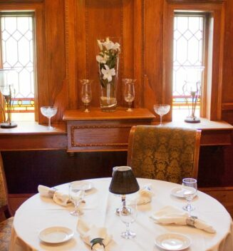 An intimate table for 2 is set in front of stained glass